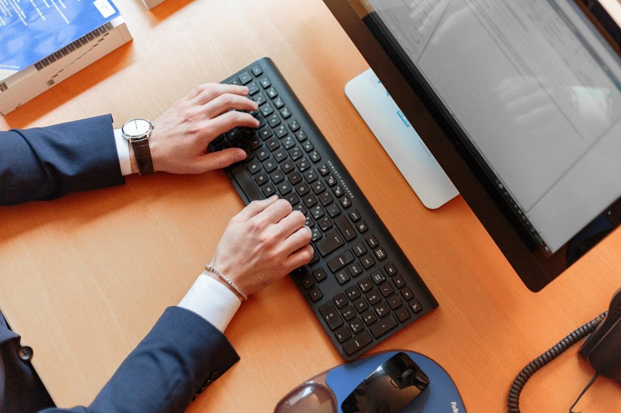 personne en costume en train de taper sur un clavier d'ordinateur fixe